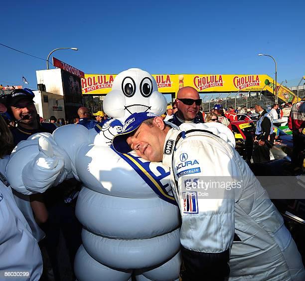 Gil de Ferran driver of the de Ferran Motorsports Acura celebrates with Bibendum the Michelin Tire mascot after winning the Tequila Patron American...