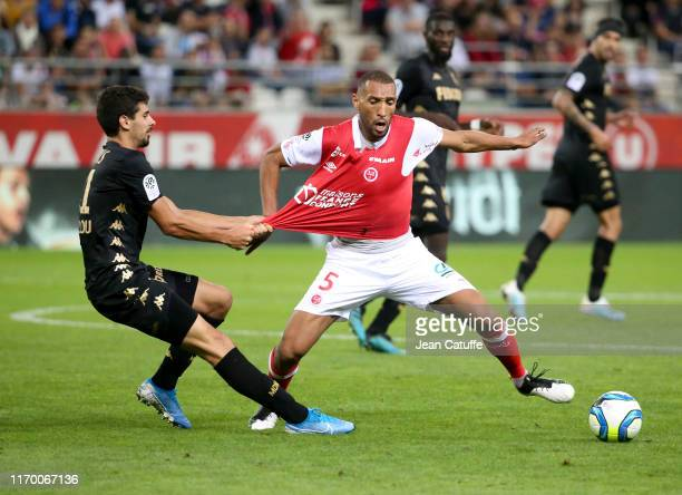 Gil Dias of Monaco pulls the jersey of Yunis Abdelhamid of Reims during the Ligue 1 match between Stade de Reims and AS Monaco at Stade Auguste...