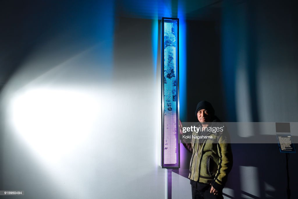 Gil Kuno poses for a photograph at the Media Ambition Tokyo at Roppongi Hills on February 8, 2018 in Tokyo, Japan. gWaterfallh is about the singularity of chaos. One can find various dualities/pluralities: dark/light, sun/moon, etc. At a waterfall, the chaos of the water is a constant throughout the day - a universal singularity. gWaterfallh makes use of flip dot display technology from the 1960Õs often used on bus and airport destination signs, and is programmed to run the animated sequence mapped from footage of a waterfall in Vienna, Austria.