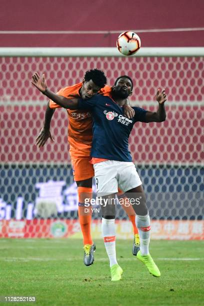 Gil of Shandong Luneng compete for a header with Diop of Beijing Renhe during the 2019 Chinese Super League match between Shandong Luneng and Beijing...