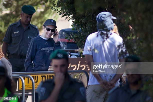 Gilad Shalit smiles as he talks on a mobile phone outside his home on October 19 2011 in Mitzpe Hila Israel Shalit was freed yesterday after being...