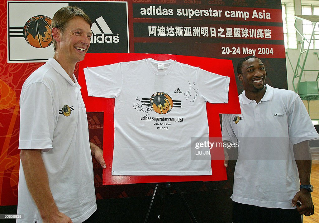 Gilbert Arenas (R) of the NBA (National Basketball Association) Washington Wizards team and the former NBA star Detlef Schrempf (L) pose with a T-shirt they signed at a press conference of the Adidas Basketball Superstar Camp in Shanghai, 20 May 2004. The camp features NBA players and professional coaches from the US, Europe and China to develop future generations of Basketball superstars. AFP PHOTO/LIU Jin