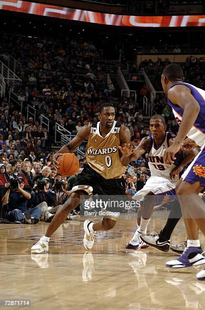 Gilbert Arenas of the Washington Wizards drives past Raja Bell of the Phoenix Suns in an NBA game played on December 22 at US Airways Center in...