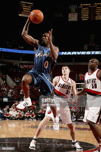 Gilbert Arenas of the Washington Wizards goes to the basket past Viktor Khryapa and Zach Randolph of the Portland Trail Blazers during the game at...