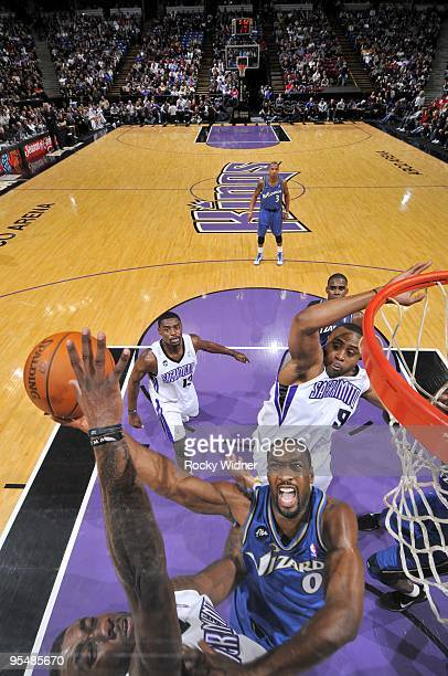 Gilbert Arenas of the Washington Wizards shoots a layup against Donte Greene and Kenny Thomas of the Sacramento Kings during the game at Arco Arena...