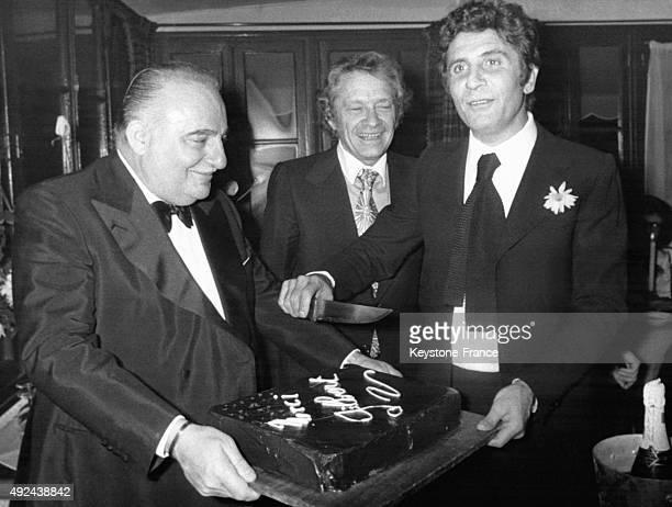 Gilbert Becaud coupe un gateau d'anniversaire pour ses 20 ans de musichall tenu par Bruno Coquatrix a l'Olympia a Paris France