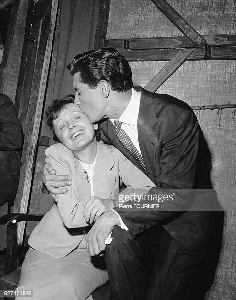 Gilbert Becaud gives singer Edith Piaf a kiss during the presentation of the Bravos du Music Hall Awards