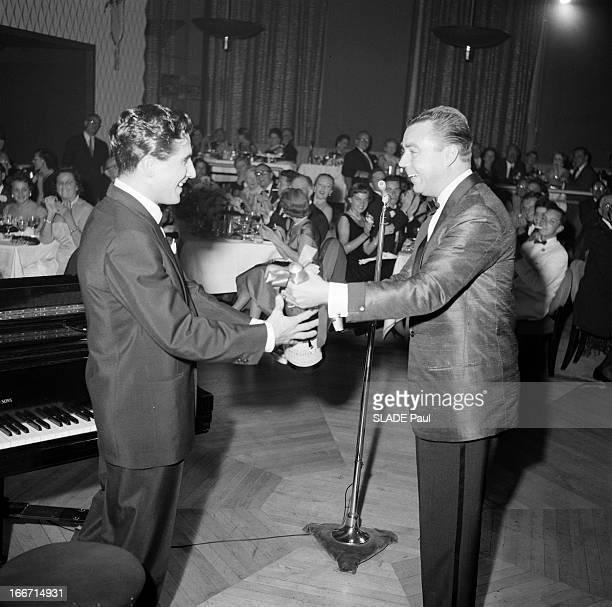 Gilbert Becaud In New York. En 1955, à New York, le chanteur et compositeur, francais Gilbert BECAUD, souriant recevant en cadeau une bouteille de...