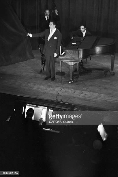 Gilbert Becaud On Stage. Lors d'une représentation, sur scène Gilbert BECAUD accompagné par un trio dont un piano et un contrebassiste tire le...