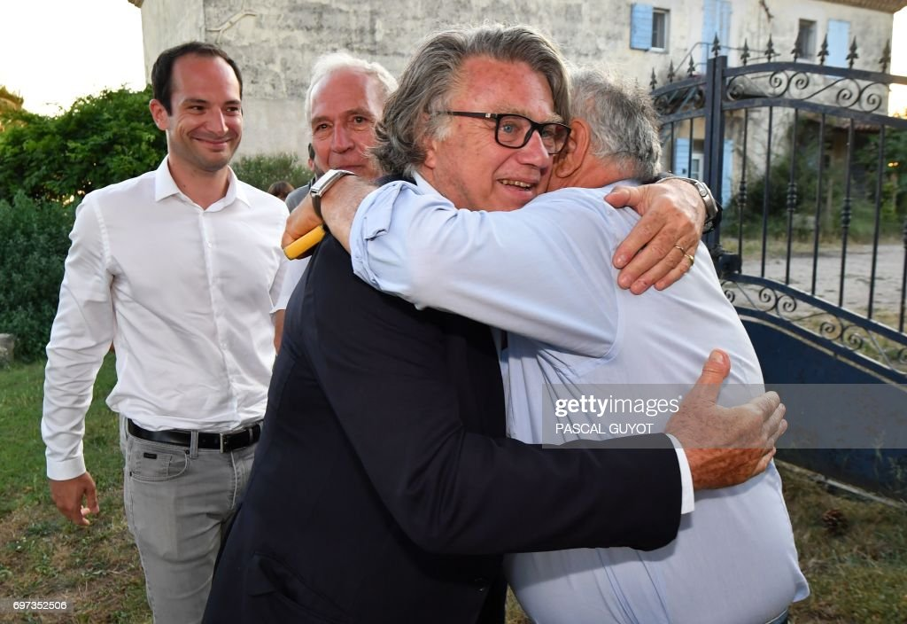 Gilbert Collard (C), French lawyer and far-right Front National (FN) party's candidate in the 2nd constituency of Gard department for the French parliamentary elections, is congratulated after winning in the second round on June 18, 2017 in Gallician, southern France. French President Emmanuel Macron's centrist party and its allies are on track for a huge majority in parliament, winning 355-425 seats in the 577-strong national assembly, polls showed on June 18. /