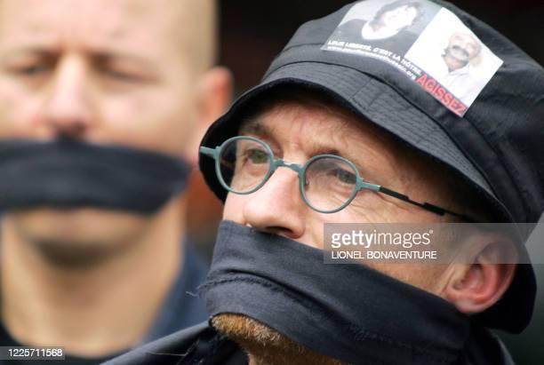 Gilbert Laval correspondant toulousain pour le quotidien Libération bâillonné et vêtu de noir participe à une manifestation de soutien à sa consoeur...