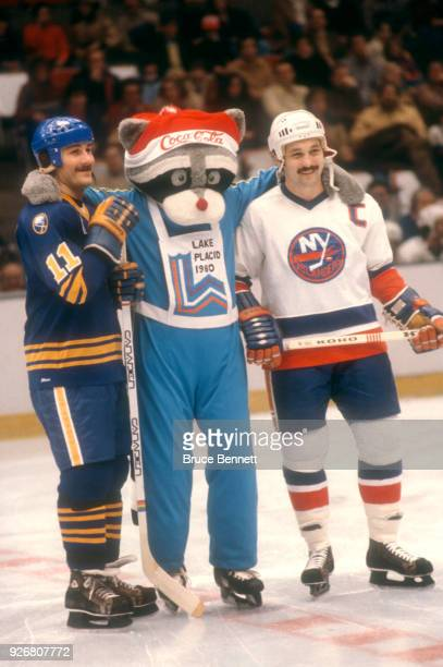 Gilbert Perreault of the Buffalo Sabres and Bryan Trottier of the New York Islanders pose with the 1980 Lake Placid Olympic mascot Roni prior to an...