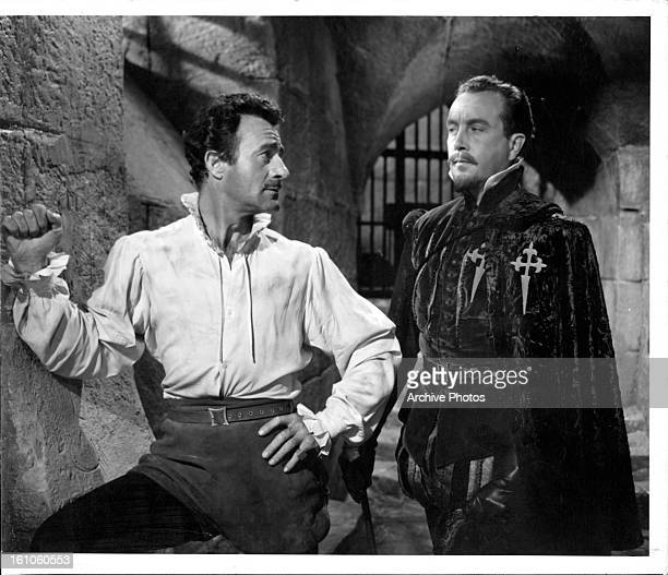 Gilbert Roland is visited in prison by Dennis Price in a scene from the film 'That Lady' 1955