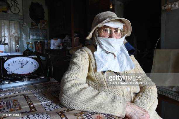 Gilberte Troquet poses in her house as she wears a makeshift mask in MontignyLeChartif western France on April 8 on the 23rd day of a lockdown in...