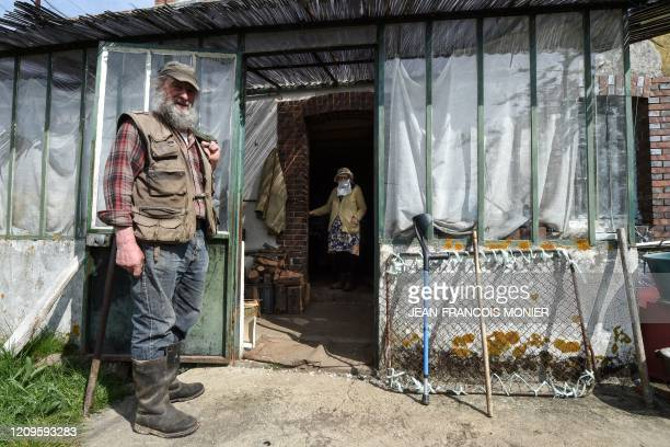 Gilberte Troquet poses wearing a makeshift mask in her house with her son JeanMichel Troquet a retired mechanic as he visits her in MontignyLeChartif...