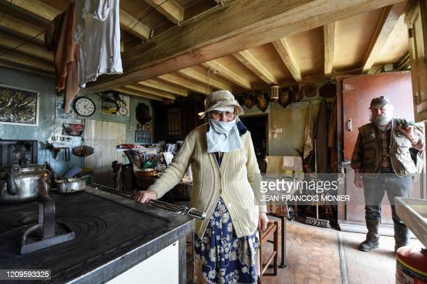 TOPSHOT Gilberte Troquet poses wearing a makeshift mask in her house with her son JeanMichel Troquet a retired mechanic as he visits her in...