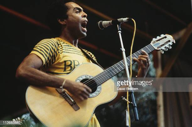 Gilberto Gil Brazilian singersongwriter and guitarist singing into a microphone while playing the guitar during a live concert performance circa 1982
