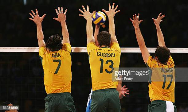 Gilberto Godoy Filho Gustavo Endres and Ricardo Garcia of Brazil jump to block the spike by Italy the men's indoor Volleyball gold medal match on...