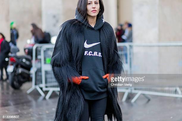 Gilda Ambrosio wearing a fur coat a black hoody and orange gloves outside Rochas during the Paris Fashion Week Womenswear Fall/Winter 2016/2017 on...