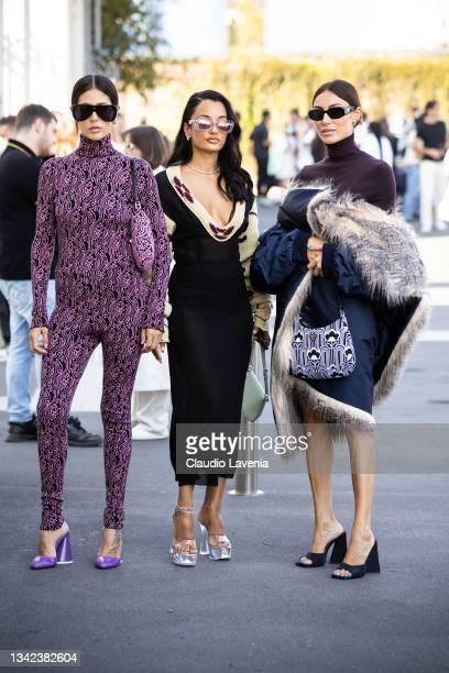 Gilda Ambrosio, wearing a purple printed jumpsuit, Amina Muaddi and Giorgia Tordini, pose ahead of the Prada fashion show during the Milan Fashion...