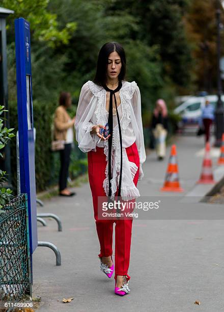 Gilda Ambrosio wearing a white blouse and red pants outside Chloe on September 29, 2016 in Paris, France.