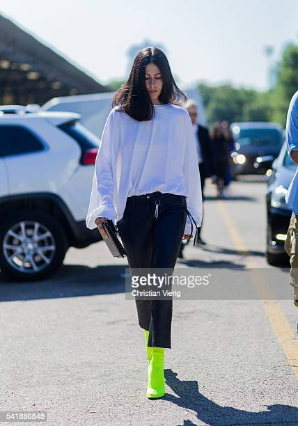 Gilda Ambrosio wearing a white shirt black leather pants and neon boots outside Diesel during the Milan Men's Fashion Week Spring/Summer 2017 on June...