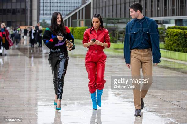 Gilda Ambrosio wearing black varnished pants knit Amina Muaddi wearing red button shirt and pants and Marc Forne wearing denim jacket is seen outside...