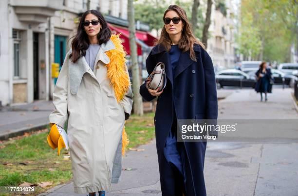 Gilda Ambrosio wearing creme white coat and Giorgia Tordini wearing navy long coat is seen outside Loewe during Paris Fashion Week Womenswear Spring...