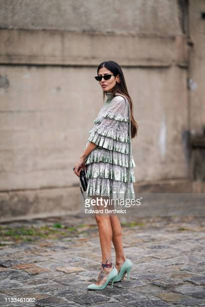 Gilda Ambrosio wears a glitter shiny ruffled dress with fringes, sunglasses, a clutch, earrings, outside Valentino, during Paris Fashion Week...