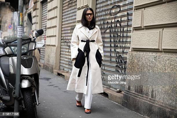 Gilda Ambrosio wears a long offwhite Sportmax coat with a black belt and pockets outside the Sportmax show during the Milan Fashion Week Fall/Winter...