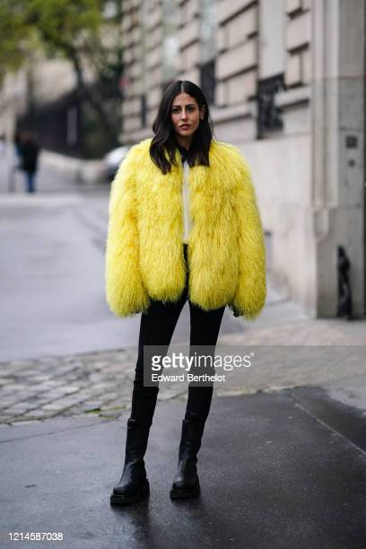 Gilda Ambrosio wears a yellow fluffy faux fur coat, black pants, black leather boots, outside Alessandra Rich, during Paris Fashion Week - Womenswear...