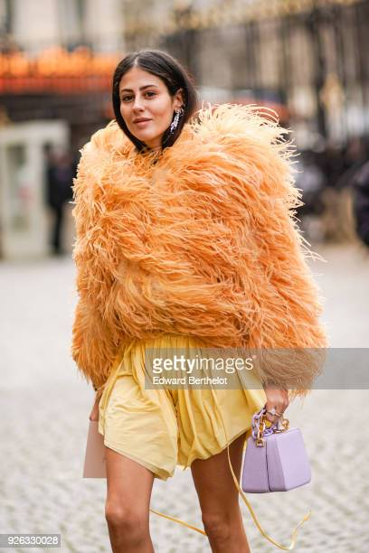 Gilda Ambrosio wears an orange fur coat a yellow skirt white shoes a purple bag and attends the Nina Ricci show as part of the Paris Fashion Week...