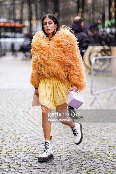 Gilda Ambrosio wears an orange fur coat, a yellow skirt, white shoes, a purple bag, and attends the Nina Ricci show as part of the Paris Fashion Week...
