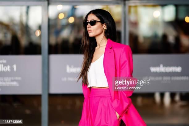 Gilda Ambrosio wears sunglasses, a white top, a neon pink pantsuit, outside Giambattista Valli, during Paris Fashion Week Womenswear Fall/Winter...