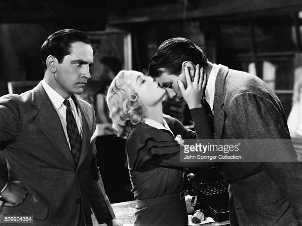 Gilda Farrell kisses painter George Curtis on the forehead as playwright Tom Chambers looks angrily on in the 1933 comedy film Design for Living