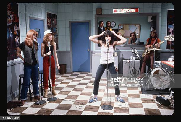 Gilda Radner does a comic impersonation of punk rock singer Patti Smith in a sketch from 'Saturday Night Live' Fellow cast members Jane Curtin and...