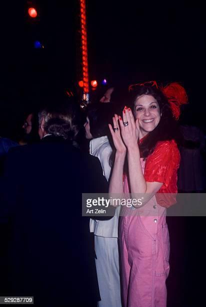 Gilda Radner wearing pink overalls clapping her hands at Studio 54 circa 1970 New York