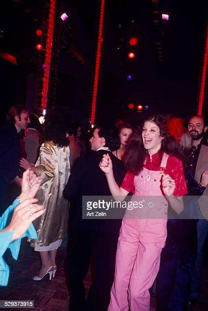 Gilda Radner wearing pink overalls dancing at Studio 54