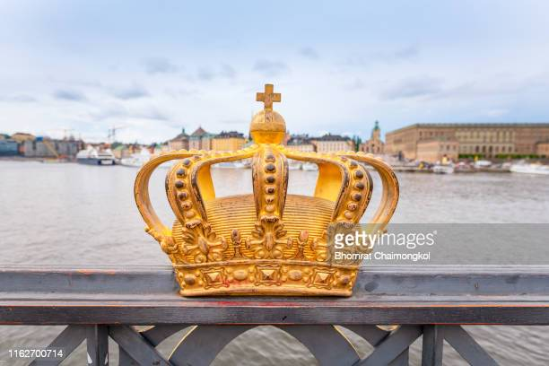 gilded crown at the middle of skeppsholmen bridge with gamla stan in the background at stockholm, sweden - koning koninklijk persoon stockfoto's en -beelden
