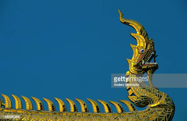 a gilded naga, the mystical serpent, adorns the roof of this buddhist temple - mythology stock pictures, royalty-free photos & images