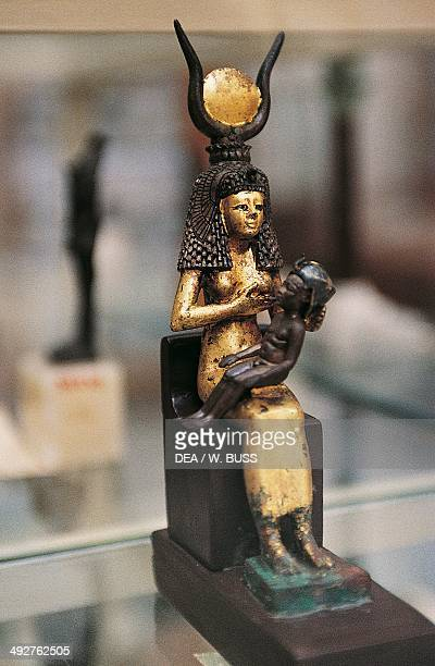 Gilded wood statuette of Isis breastfeeding infant Horus From the Treasure of Tutankhamun Egyptian civilization New Kingdom XVIII Dynasty Cairo...