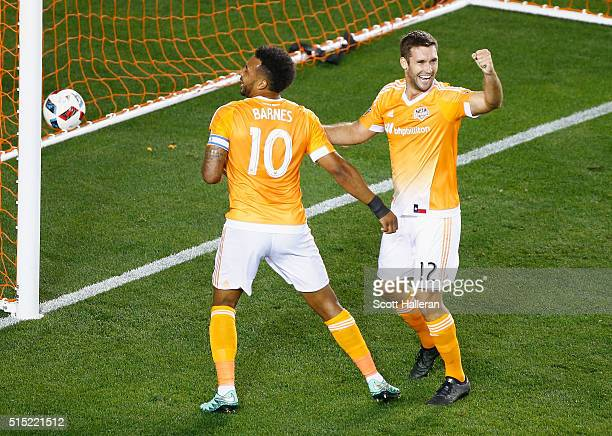 Giles Barnes of and Will Bruin of the Houston Dynamo celebrate a firsthalf own goal against FC Dallas during their game at BBVA Compass Stadium on...