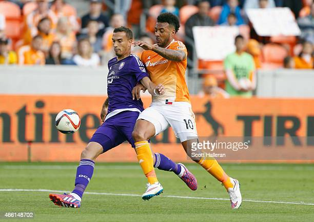 Giles Barnes of Houston Dynamo battles for the ball with Seb Hines of Orlando City SC during their game at BBVA Compass Stadium on March 13, 2015 in...