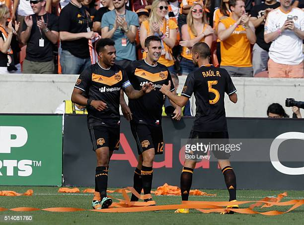 Giles Barnes of Houston Dynamo celebrates with Will Bruin and Raul Rodriguez after scoring against the New England Revolution in the second half at...