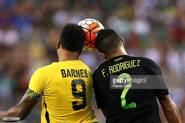 Giles Barnes of Jamaica and Francisco Javier Rodriguez of Mexico battle for a head ball in the first half during the CONCACAF Gold Cup Final at...