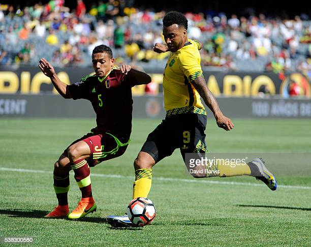 Giles Barnes of Jamaica kicks the ball as Arquimedes Figuera of Venezuela defends during the first half during a group C match between Jamaica and...
