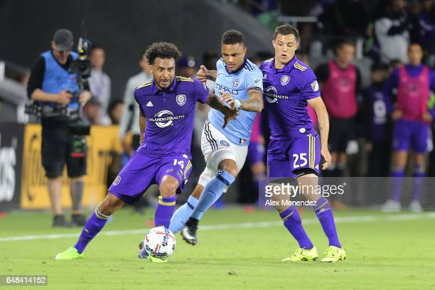 Giles Barnes of Orlando City SC dribbles the ball past Sean Okoli of New York City FC and Donny Toia of Orlando City SC during a MLS soccer match...