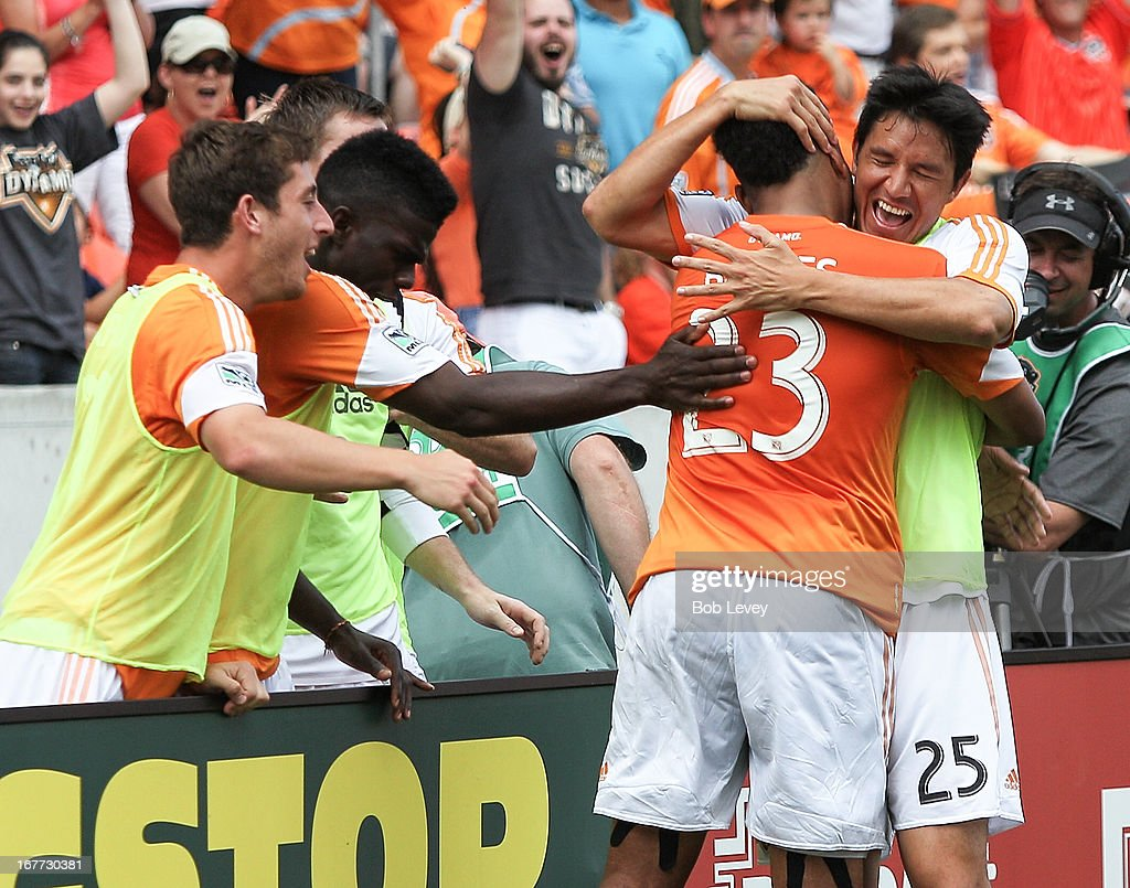 Giles Barnes #23 of the Houston Dynamo is congratuated by Brian Ching #25 of the Houston Dynamo and his teammate after scoring in the second half against the Colorado Rapids at BBVA Compass Stadium on April 28, 2013 in Houston, Texas.