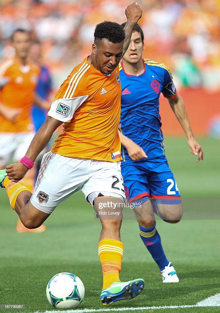 Giles Barnes #23 of the Houston Dynamo scores as he gets behind Nathan Sturgis #24 of the Colorado Rapids in the second half at BBVA Compass Stadium on April 28, 2013 in Houston, Texas.