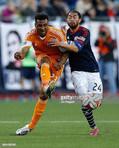 Giles Barnes of the Houston Dynamos is defended by Lee Nguyen of the New England Revolution in the 2nd half at Gillette Stadium on April 12 2014 in...